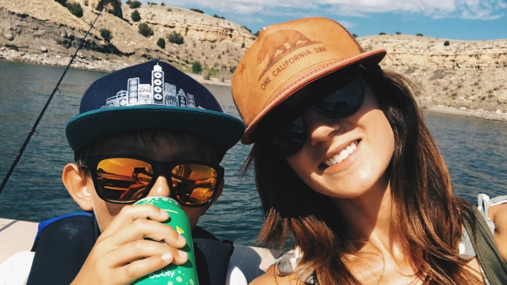 moms and son on a boat smiling at the camera
