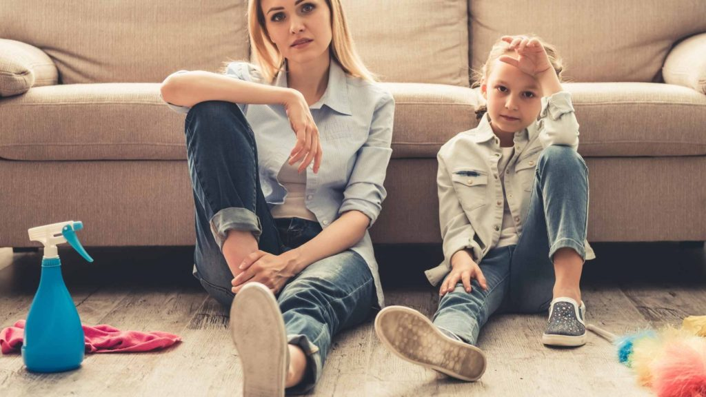 mom and daughter sitting in front of a couch looking tired