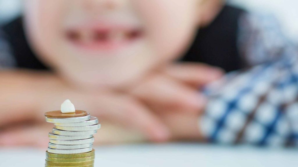 child sitting behind a stack of coins with a tooth on it