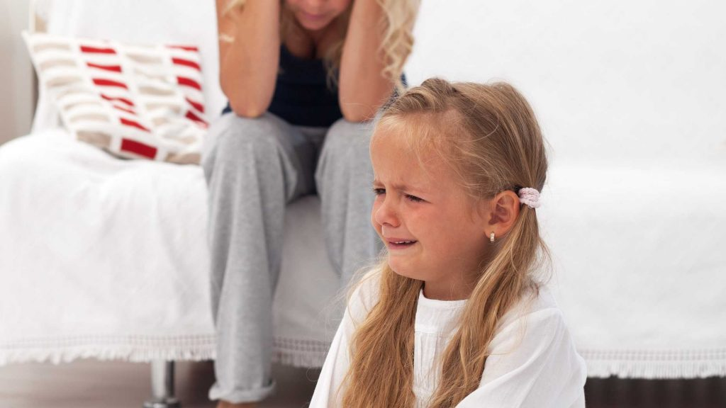 Frustrated mom with crying little girl
